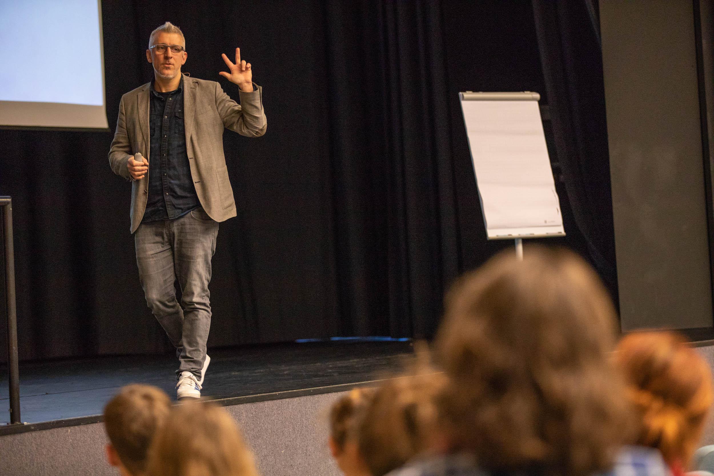 coach mit Flipchart auf Bühne und vor Publikum
